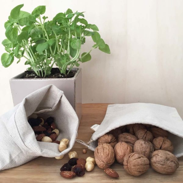 Small recycled cotton produce bag with dried fruit and basil plant