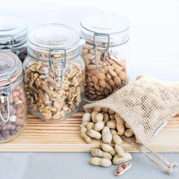 Bolsa de tela de yute con cacahuetes dentro y botes herméticos con frutos secos sobre tabla de madera