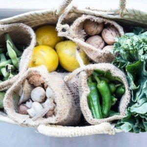 Cesta mimbre con bolsas de tela de yute Verdonce con verduras, frutos secos y limones