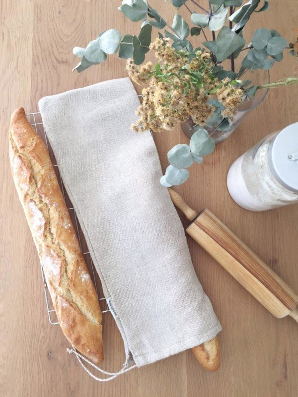Reusable bread bag with rustic baguette and rolling pin on table
