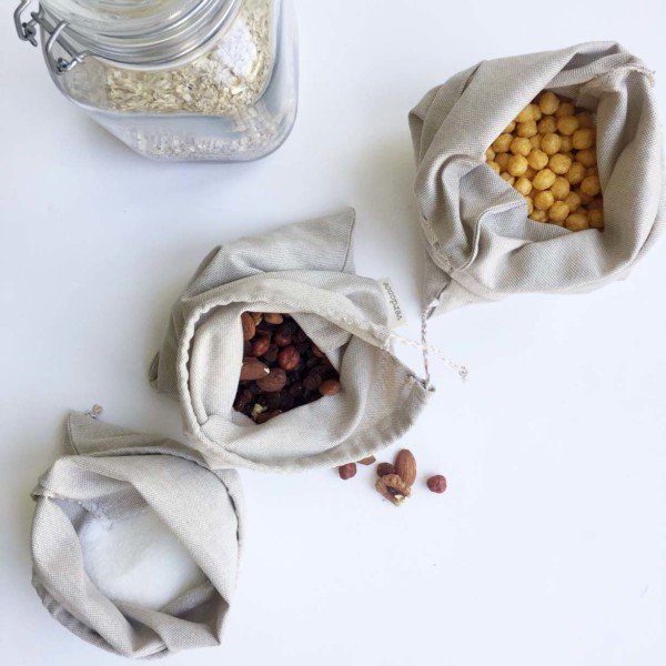 Reusable natural cotton and linen bags holding unpacked food
