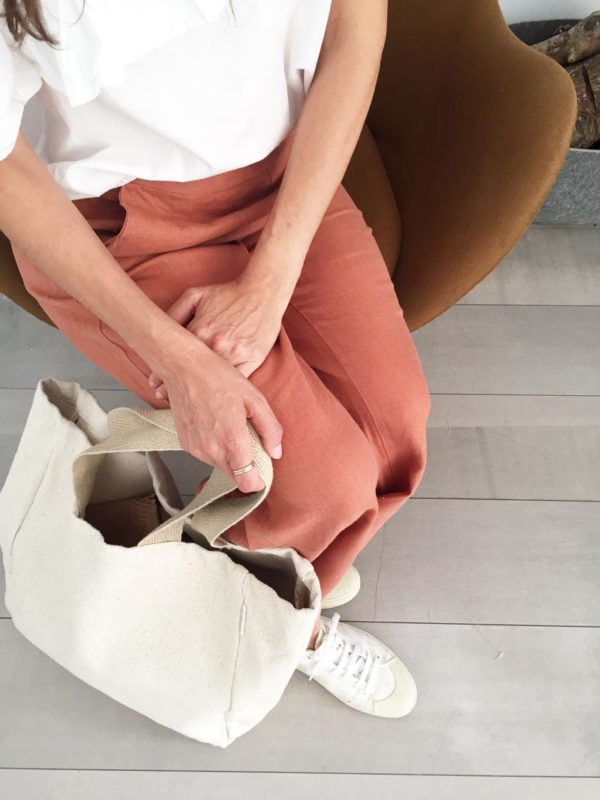 Woman sitting in armchair with Verdonce minimalist canvas tote at feet