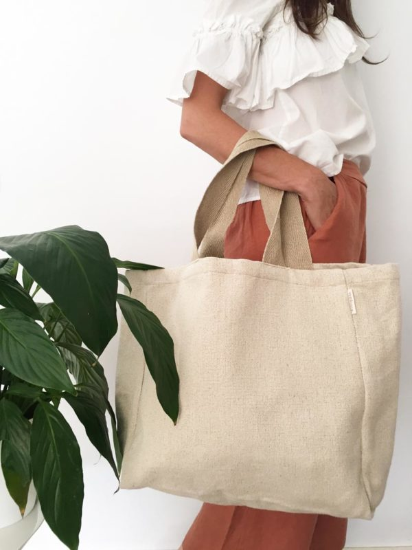 Woman poses with Verdonce minimalist canvas tote bag at hip height