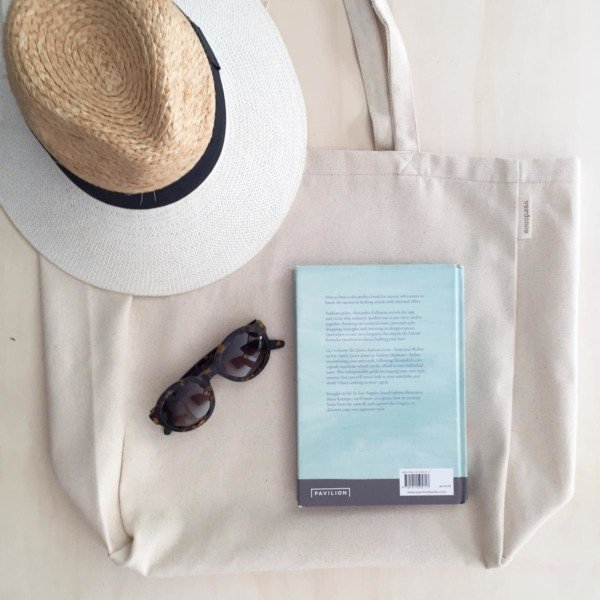 Minimalist canvas tote bag on table with hat sunglasses and book