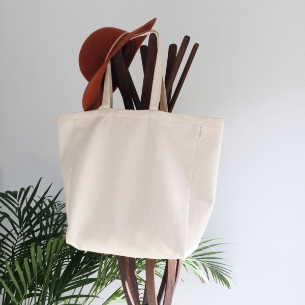 Minimalist zero waste canvas tote bag hanging on coat stand with hat