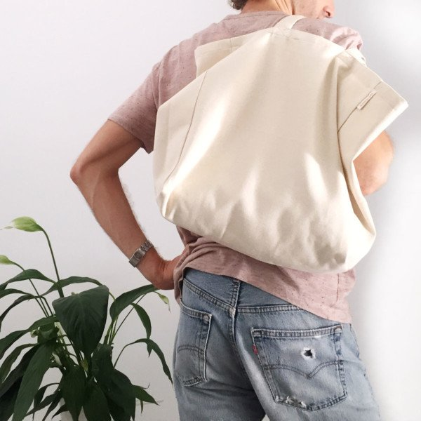 Male carrying minimalist canvas tote bag over shoulder
