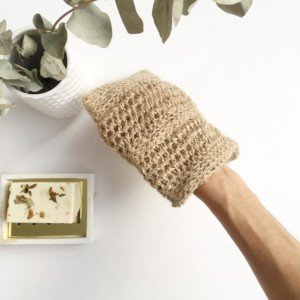 Natural jute peeling glove with hand inside and bar of soap