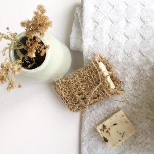 Bar of soap inside natura jute soap bag with towel and vase of dried flowers