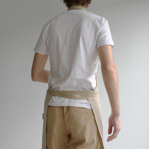 Shot of man from behind showing apron straps crossed to tie at front