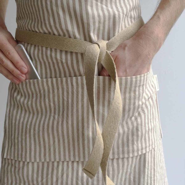 Close up man taking phone out of apron pocket