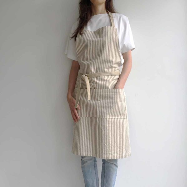 Woman wearing striped recycled cotton apron with hemp straps