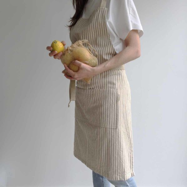 Woman wearing recycled cotton apron holding jute mesh bag with lemons