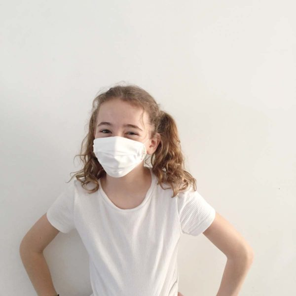 Girl wearing a white reusable plastic-free face mask made from sustainable Lyocell fabric