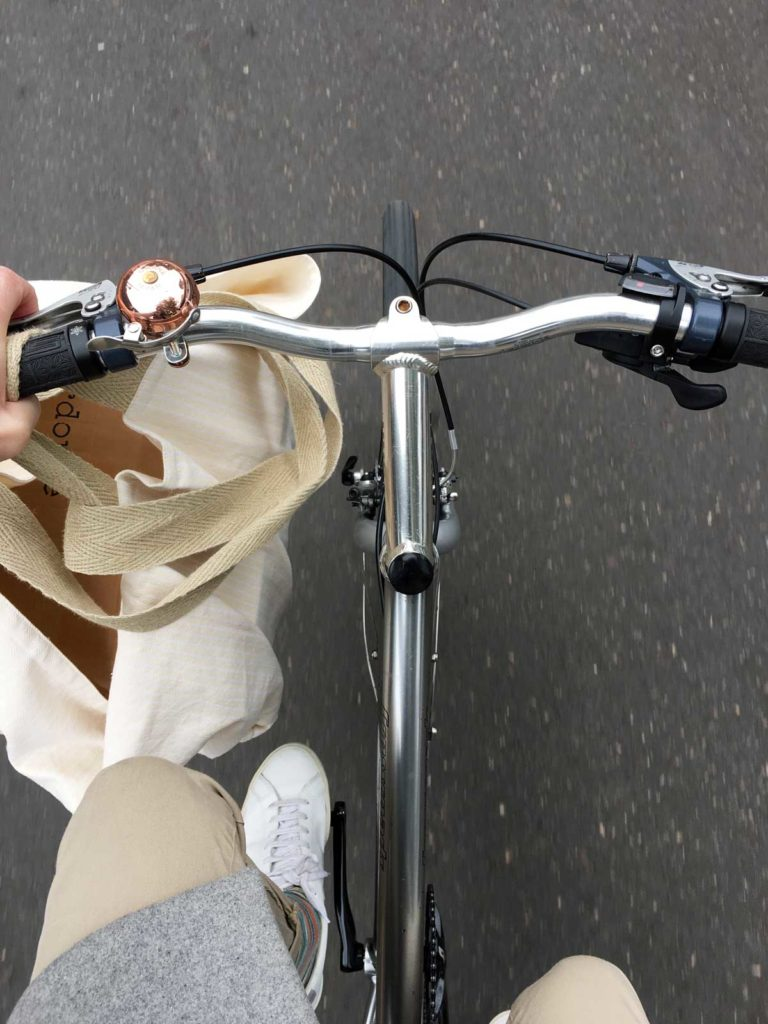 Transporting Verdonce sustainable homeware in a cloth bag bag on bike handlebars