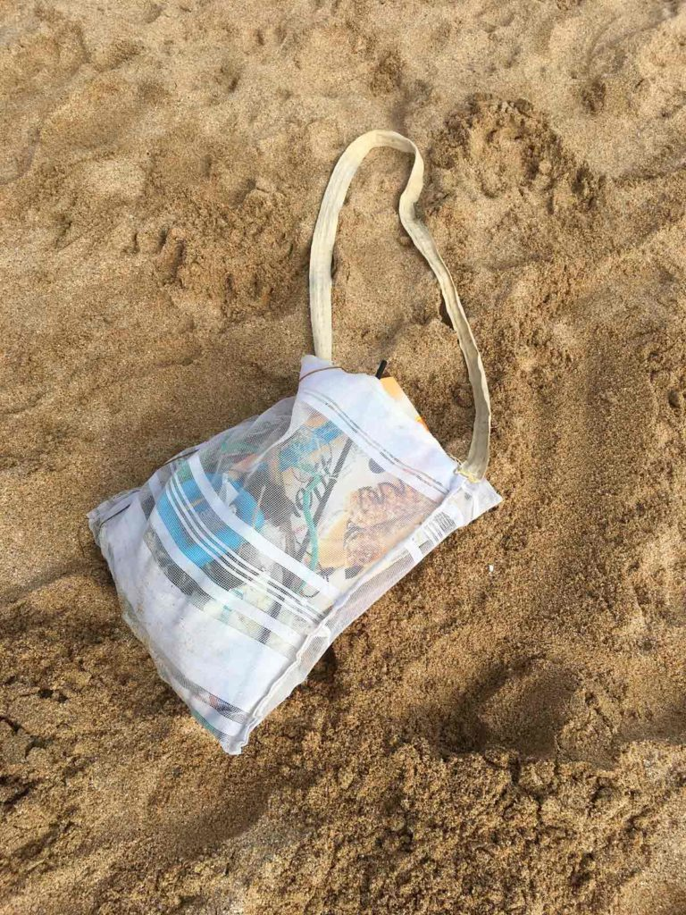 net bag on beach with plastic waste inside