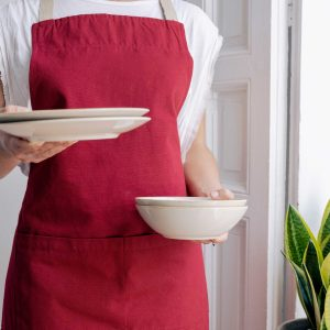 woman holding plates wearing verdonce recycled cotton apron in red wine colour