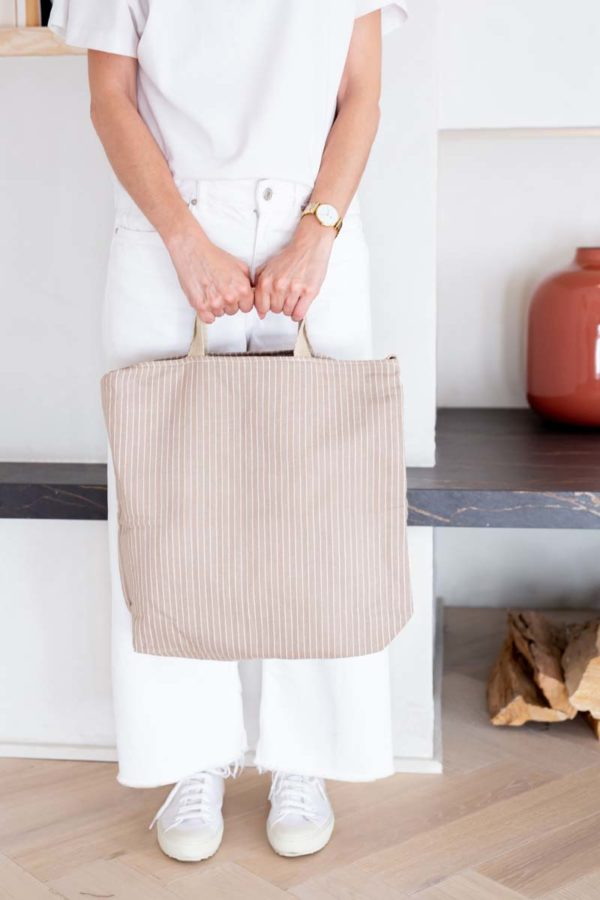 Woman holds Verdonce crossbody recycled cotton tote in earth beige herringbone