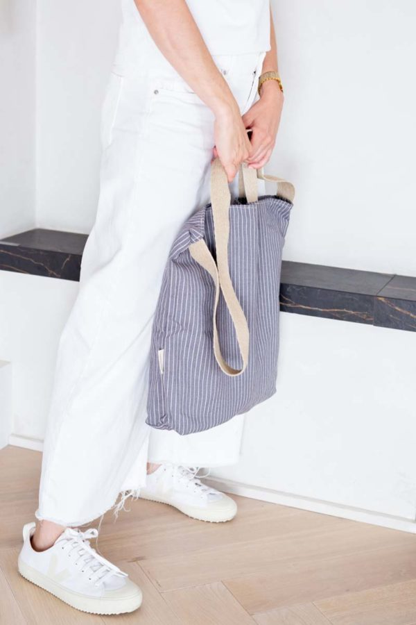 Woman holding Verdonce crossbody tote with short handles in deep sea blue herringbone colour