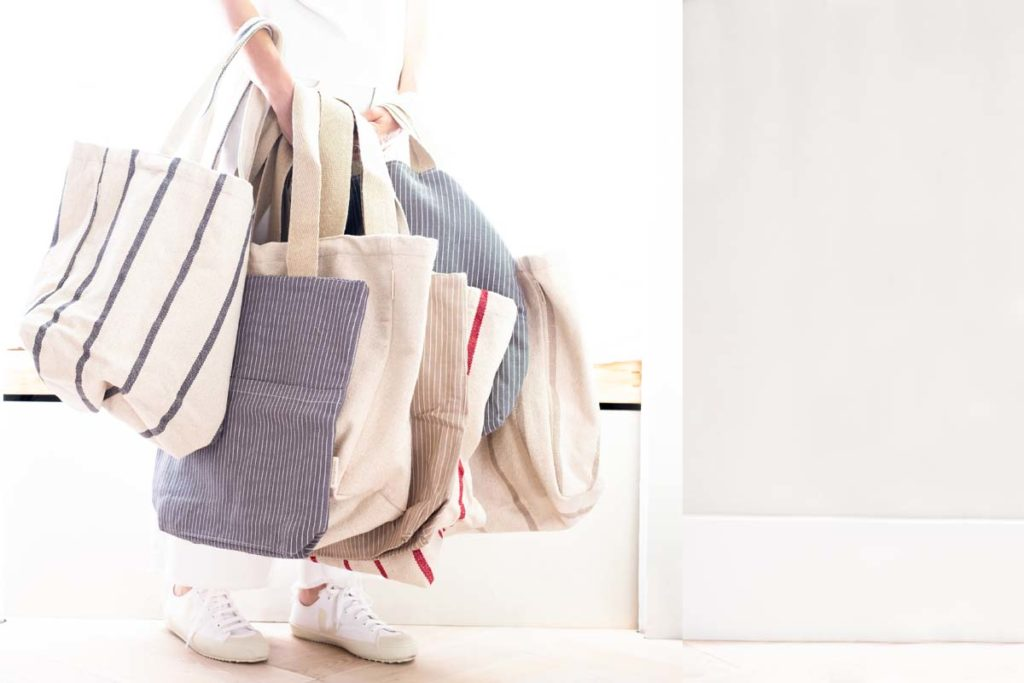 Woman carrying selection of natural recycled cotton tote bags