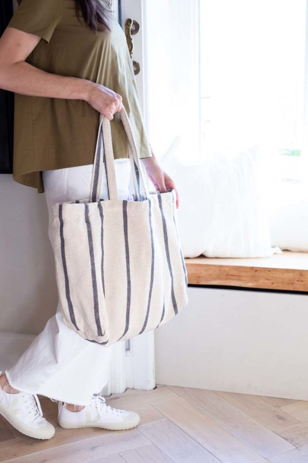 Woman looking out of window carrying verdonce maxi tote bag with grey stripes