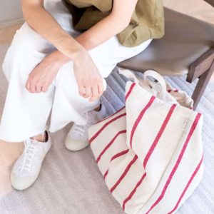 Woman sitting on a chair with a red striped tote bag at her side