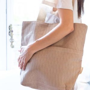Woman carrying Verdonce recycled cotton pockets tote on shoulder in earth herringbone colour