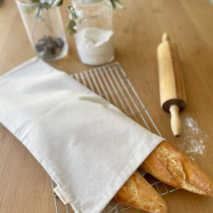Recycled cotton bread bad with two french sticks on table with rolling pin and jar of flour