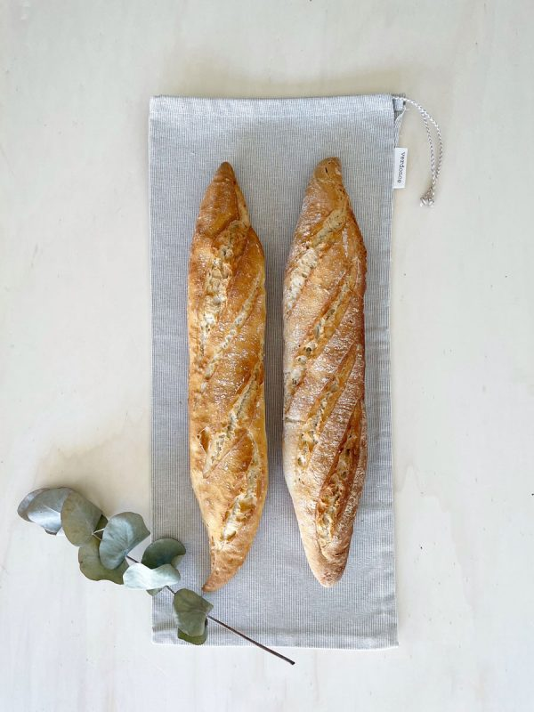 Two french sticks lying on a recycled cotton bread bag