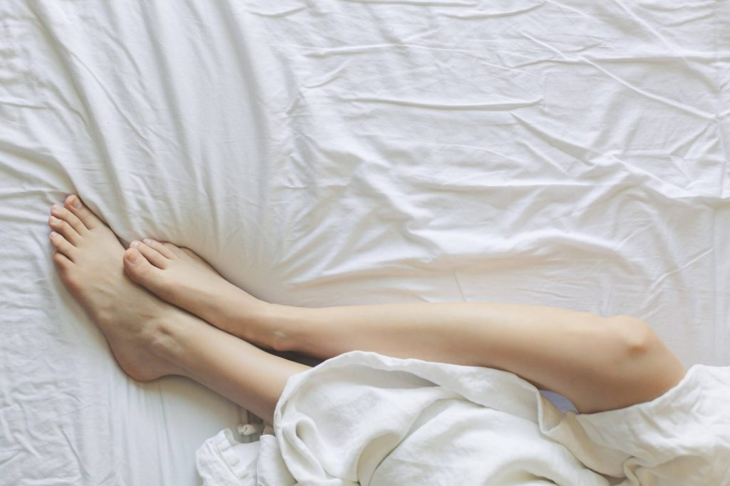 Woman's legs and feet sticking out from under a bedsheet