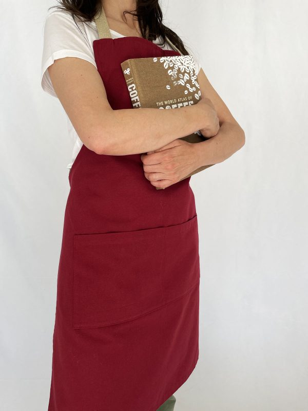 Woman holds coffee world atlas book and wearing maroon coloured recycled cotton apron by verdonce