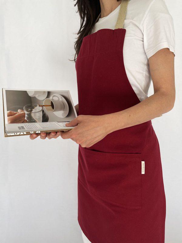 Woman holding coffee book wears eco apron in maroon