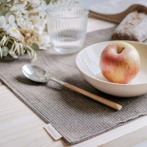 Table set with verdonce recycled cotton placemat in acorn brown colour and showing wish apple and floral arrangement
