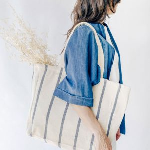 woman carrying a canvas natural cotton tote over shoulder