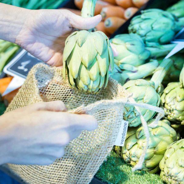 Metiendo una alcachofa en una bolsa de tela de yute de Verdonce en una frutería