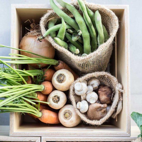 Cajon de madera con verduras y bolsas de tela de yute verdonce