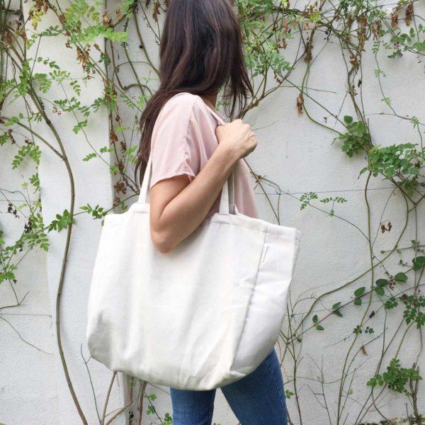 Chica con bolsa de tote minimalista en jardín