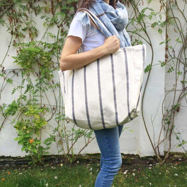 Mujer en jardín con tote sostenible con rayas