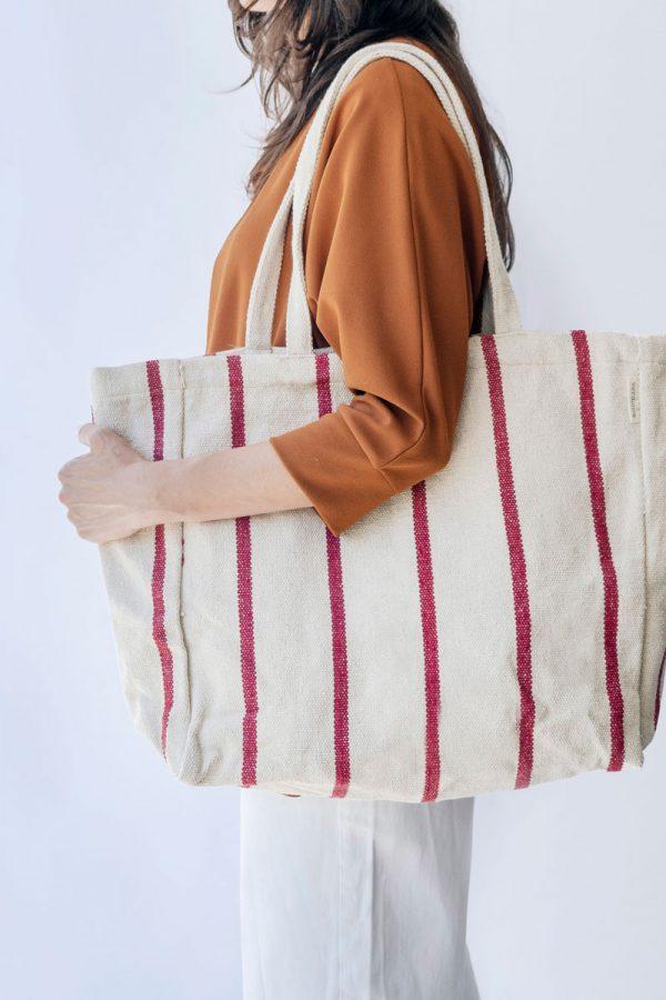 Mujer lleva bolsa canvas en hombro con rayas rojas