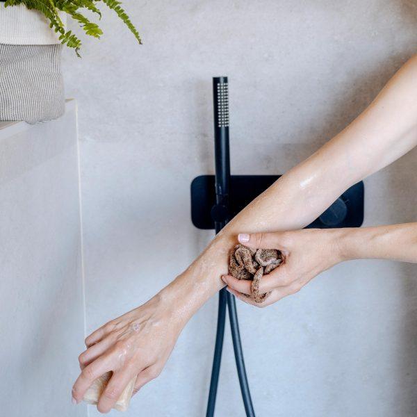 mujer en ducha con esponja natura de fibra de yute de verdonce frotando brazo