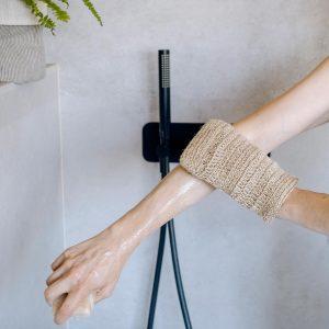 mujer frota el brazo en la ducha con la manopa de yute natural de verdonce