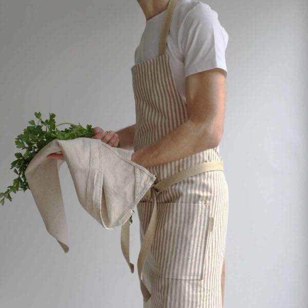 Un hombre lleva puesto un delantal de algodón reciclado y lleva hierbas de cilantro en la mano y un trapo de cocina