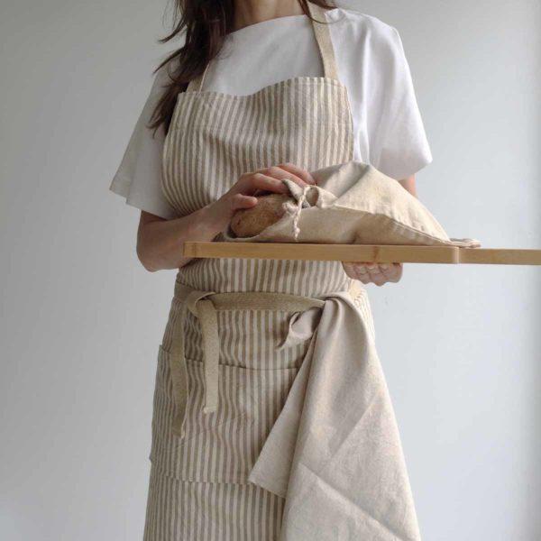 Mujer sirva pan recién hecho y lleva puesto un delantal eco de rayas y un trapo de cocina de algodón reciclado