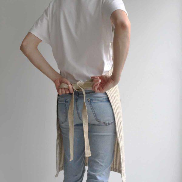 Mujer ata su delantal con tiras de cáñamo
