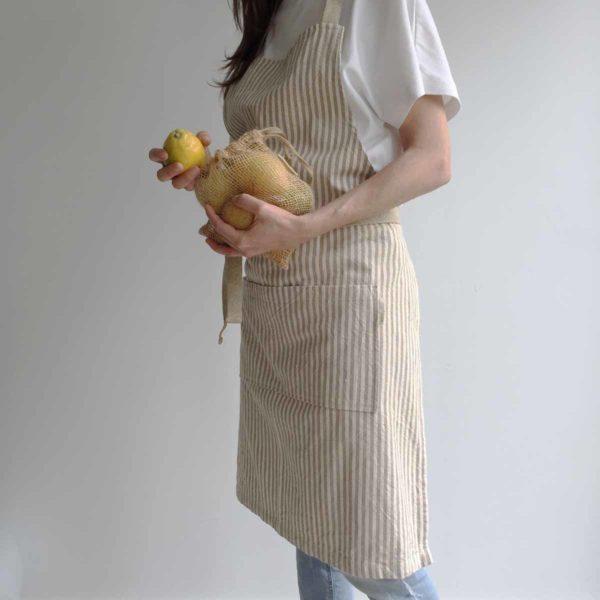 Mujer lleva bolsa de yute con limones y lleva puesto un delantal de rayas