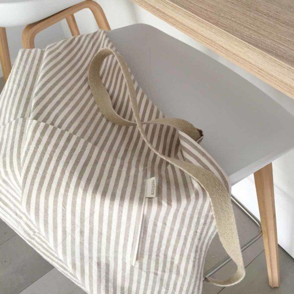 Delantal de algodon reciclado en taburete de cocina