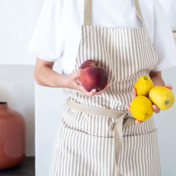 Mujer con delantal eco verdonce lleva limones y manzanas