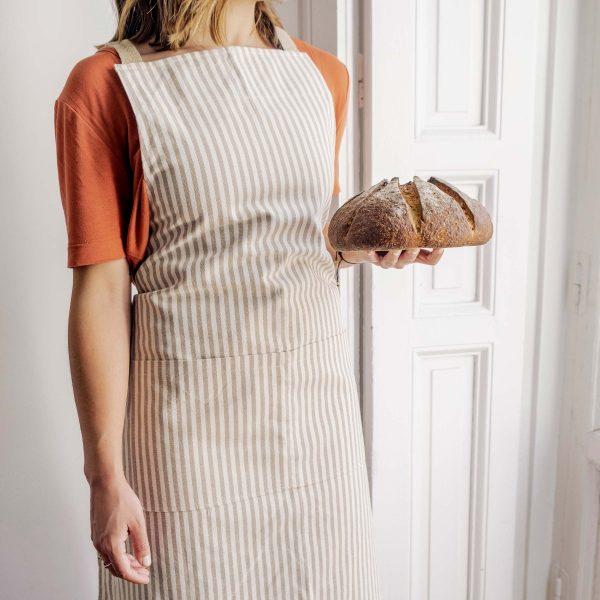 mujer con pan hogaza lleva delantal Verdonce de algodón reciclado color almendra-avena