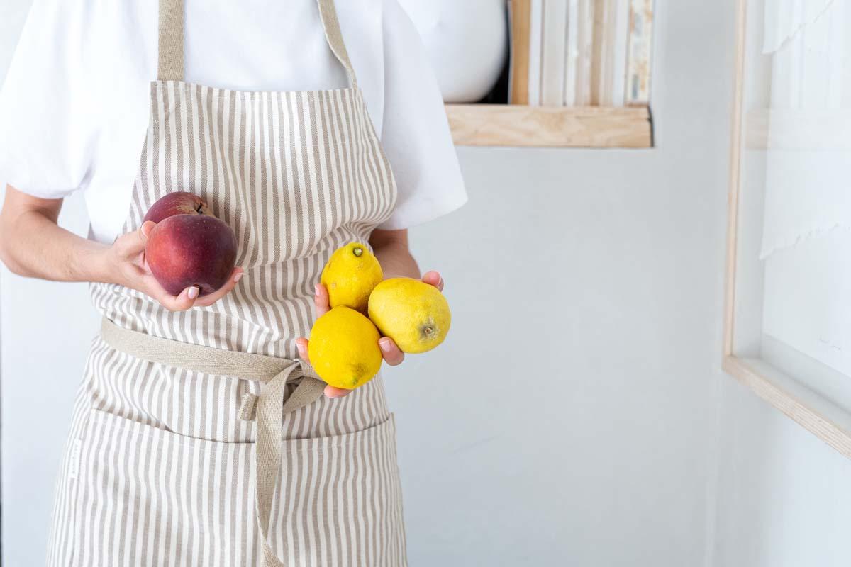 Mujer lleva delantal eco verdonce con manzanas y limones
