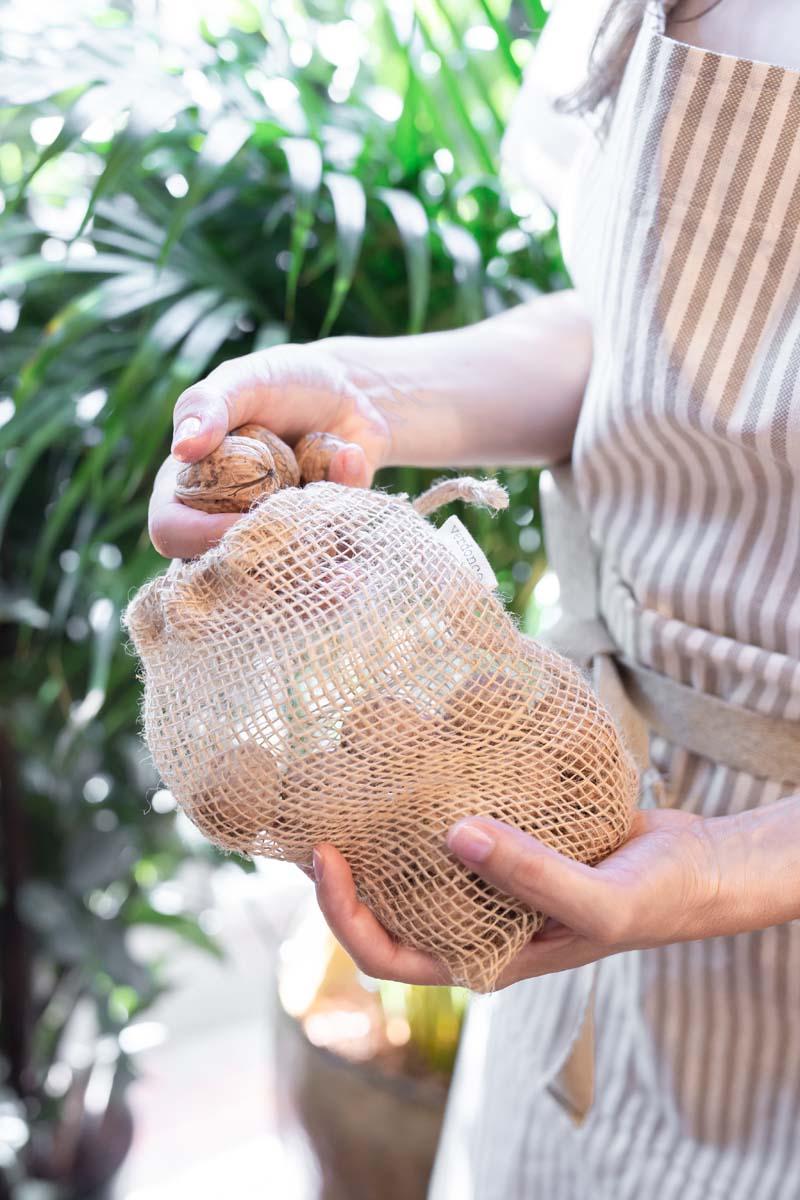 Poner nueces en una bolsa de malla de yute verdonce
