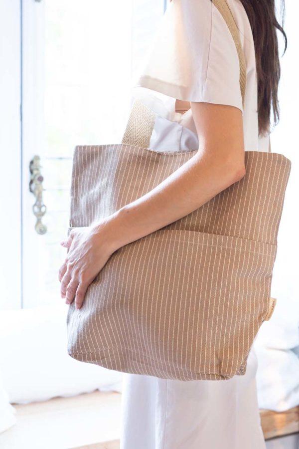Mujer mira por la ventana y lleva una bolsa tote de algodón reciclado color tierra con dibujo rayado espiga